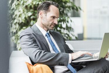 Businessman sitting in lobby using laptop - UUF12095