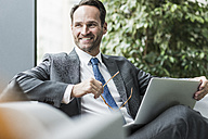 Portrait of smiling businessman sitting in lobby with laptop - UUF12098