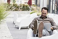 Businessman sitting on terrace using laptop - UUF12110