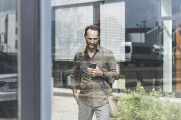 Smiling businessman using smartphone and earphones - UUF12116