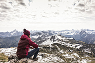 Germany, Bavaria, Oberstdorf, hiker sitting in alpine scenery - UUF12126