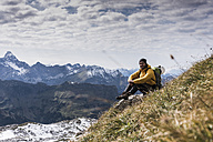 Germany, Bavaria, Oberstdorf, smiling hiker sitting in alpine scenery - UUF12138