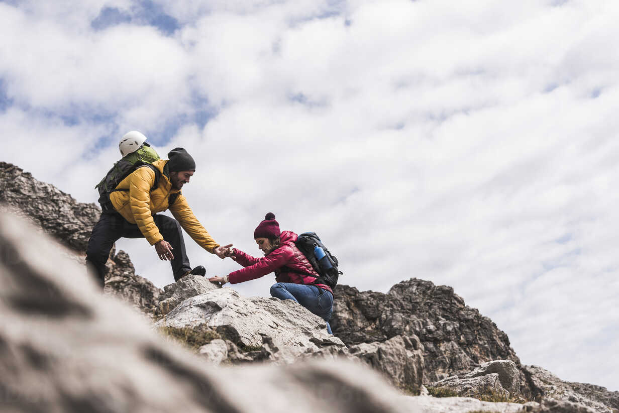 Germany, Bavaria, Oberstdorf, man helping woman climbing up rock - UUF12144 - Uwe Umstätter/Westend61