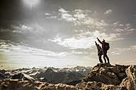 Germany, Bavaria, Oberstdorf, two hikers cheering on rock in alpine scenery - UUF12159