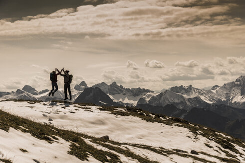 Germany, Bavaria, Oberstdorf, two hikers jumping in alpine scenery - UUF12168