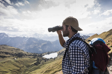 Germany, Bavaria, Oberstdorf, hiker with binoculars in alpine scenery - UUF12174