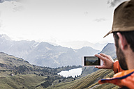 Germany, Bavaria, Oberstdorf, hiker taking picture in alpine scenery - UUF12198