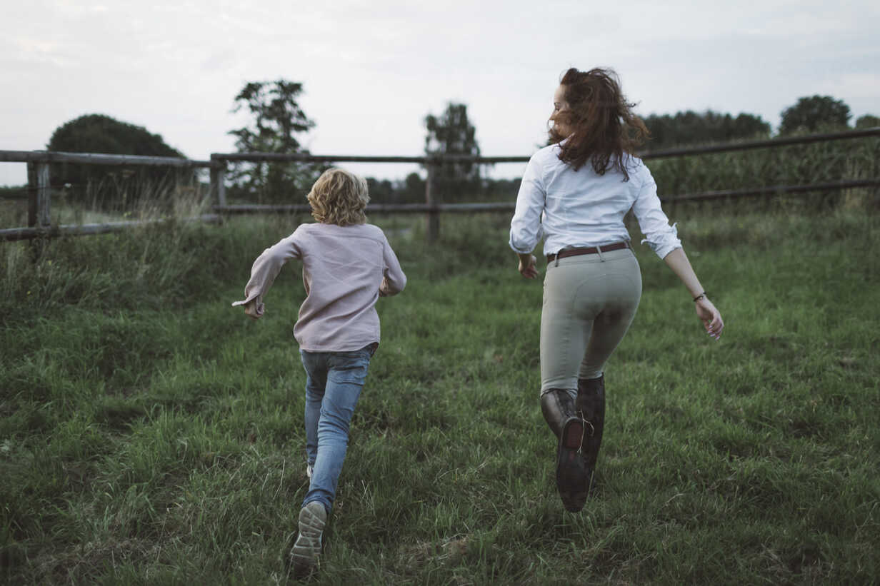 Back view of boy and young woman running side by side on a paddock - KMKF00041 - Katharina Mikhrin/Westend61
