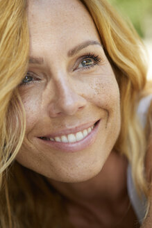 Portrait of happy strawberry blonde woman with freckles - PNEF00223