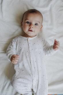 Portrait of baby boy wearing sleepers lying on bed - MOMF00286