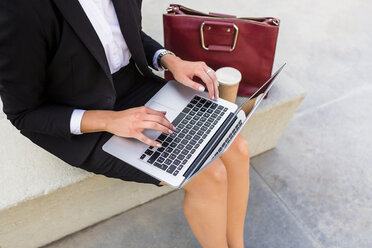 Businesswoman with fashionable leatherbag and coffee to go sitting on bench using laptop, partial view - MGIF00185