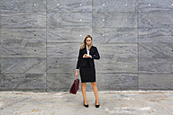 Businesswoman wearing ladies' suit checking the time - MGIF00188