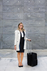 Portrait of smiling businesswoman with suitcase wearing trench coat - MGIF00191