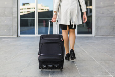 Back view of walking businesswoman with rolling suitcase - MGIF00194