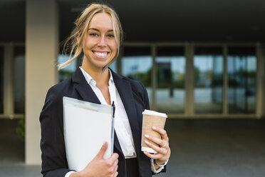 Portrait of happy businesswoman with documents and coffee to go - MGIF00197