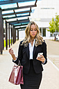 Businesswoman with fashionable leatherbag looking at cell phone - MGIF00200