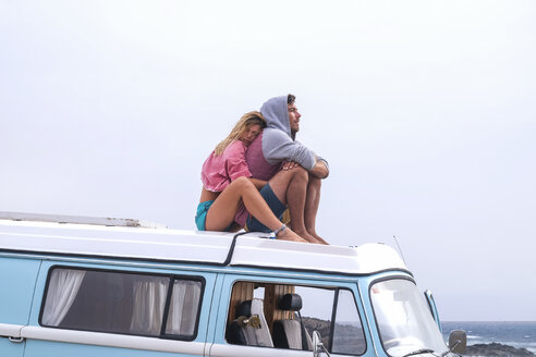 Spain, Tenerife, young couple in love  relaxing on car roof of van - SIPF01829
