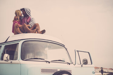 Spain, Tenerife, young couple in love  sitting on car roof of van - SIPF01832