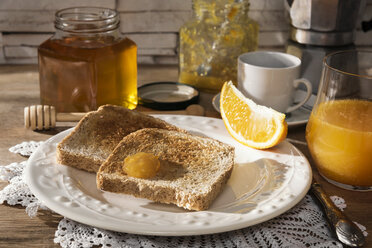 Breakfast table with toast, orange marmalade, honey, orange juice and espresso - CSTF01437