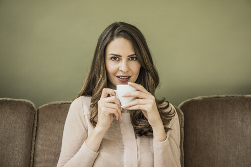 Portrait of woman sitting on couch drinking cup of coffee - MOEF00184
