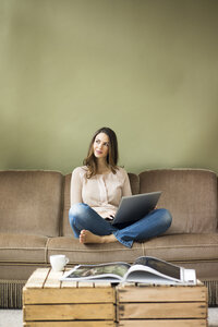 Smiling young woman sitting on couch using laptop - MOEF00187