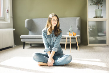 Young woman sitting on the floor in the living room - MOEF00196