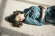 Portrait of oung woman lying on carpet in the living room enjoying sunlight - MOEF00199
