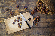 Sweet chestnuts in basket and on chopping board, knife - LVF06359