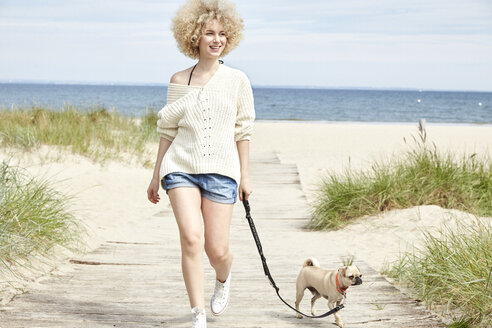 Portrait of smiling young woman going walkies with her dog on the beach - TSFF00142