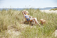 Happy young woman sitting on beach chair in the dunes - TSFF00148