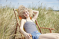 Portrait of happy young woman sitting on beach chair in the dunes - TSFF00151