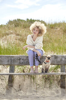 Portrait of smiling young woman sitting on bench in the dunes with her dog - TSFF00154