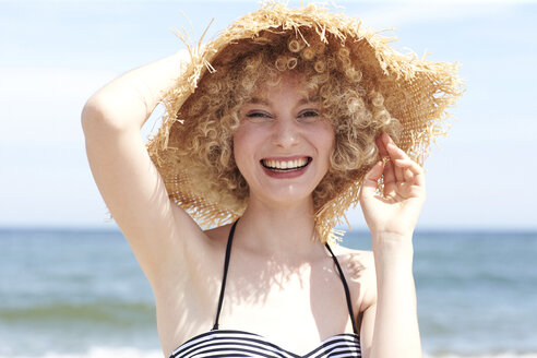 Portrait of laughing young woman wearing straw hat on the beach - TSFF00157