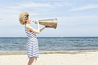 Young woman with megaphone on the beach - TSFF00166