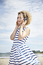 Portrait of young blond woman with headphones on the beach - TSFF00169