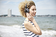 Portrait of young blond woman with headphones on the beach - TSFF00172