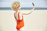 Young woman with curly blond hair taking selfie on the beach - TSFF00181