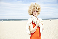 Portrait of young woman with curly blond hair on the beach - TSFF00184