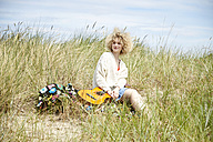 Portrait of young woman with guitar relaxing in beach dunes - TSFF00187