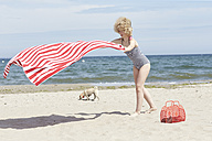 Young woman with blowing beach towel at seaside - TSFF00199