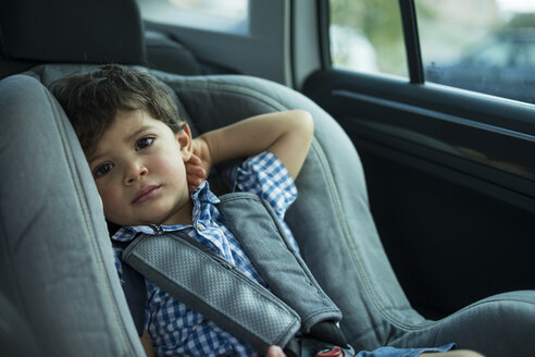 Portrait of toddler sitting in child's seat in a car - JASF01846