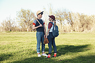 Young couple with baseball equipment in park - RTBF01079