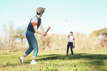 Young couple playing baseball in park - RTBF01088