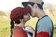 Young couple with baseball equipment kissing in park - RTBF01091