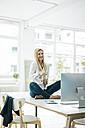 Happy businesswoman sitting on desk in office - MOEF00215