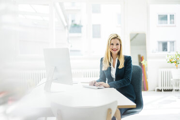 Smiling businesswoman sitting at desk in office - MOEF00218