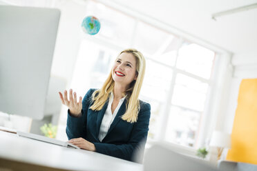 Smiling businesswoman at desk throwing up mini globe - MOEF00221