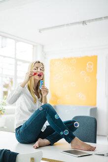 Businesswoman sitting on desk in office blowing soap bubbles - MOEF00230