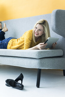 Happy woman lying on couch using tablet - MOEF00233
