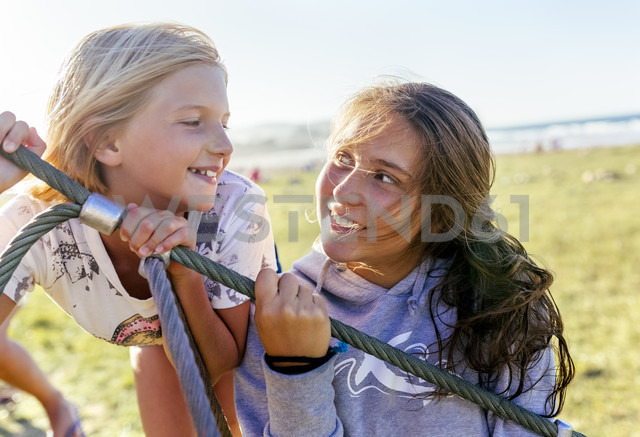 Two happy girls looking at each other - MGOF03659